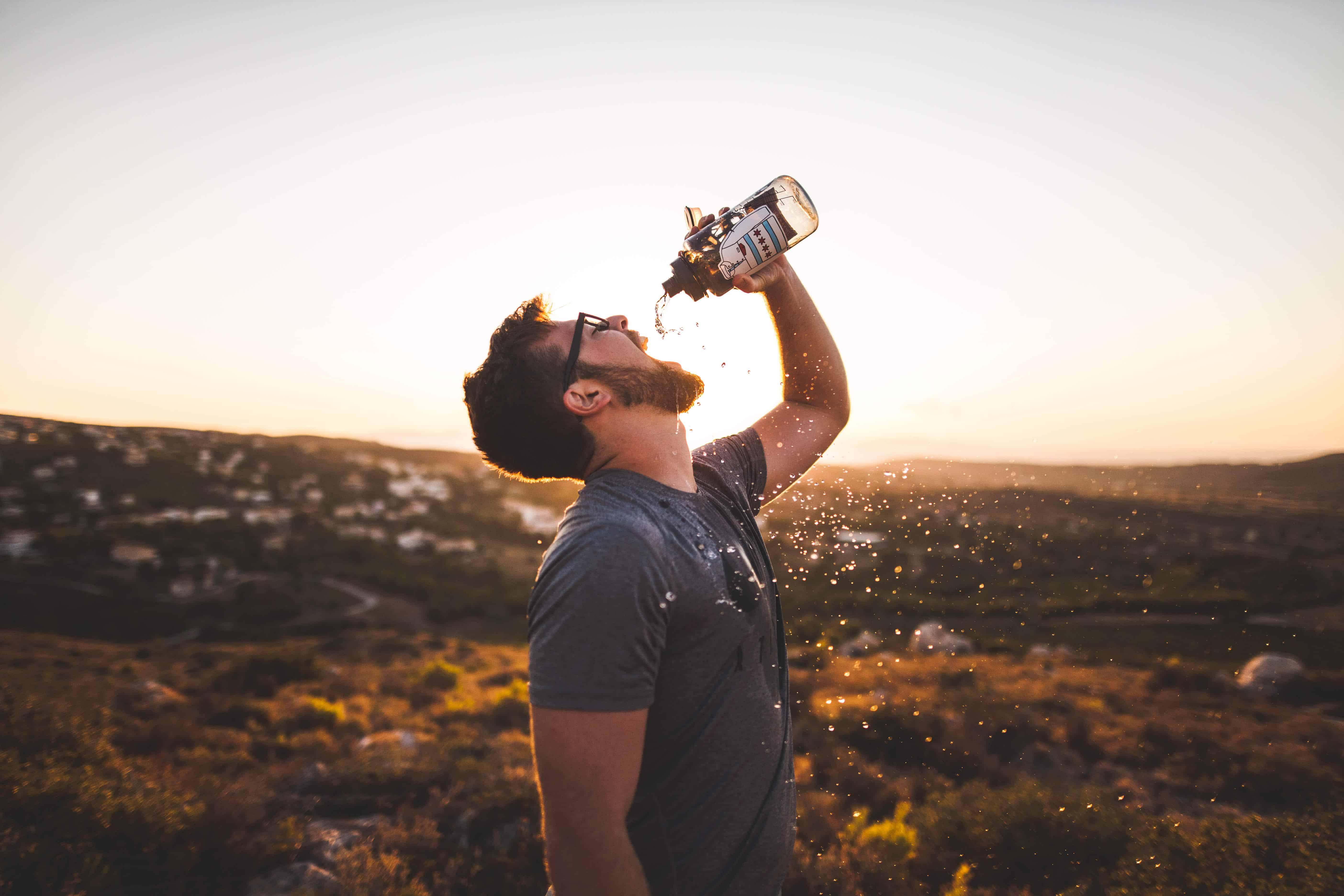 man drinks water in fall